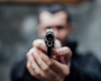 A man pointing a gun at lens