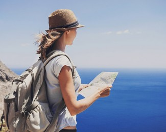 Woman traveler with map looking at the sea, travel concept